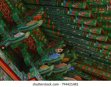 Detail of the roof of a buddhist temple with green red and blue floreal pattern. Jeju Island, Korea