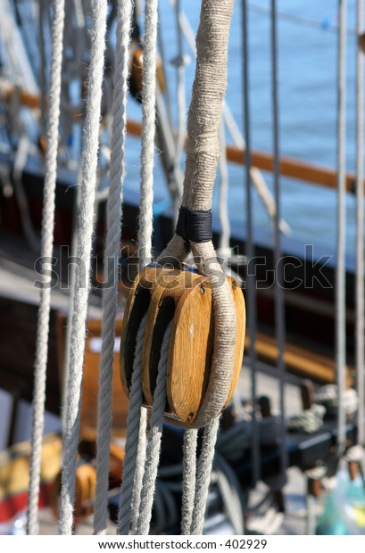 Detail of Ropes and Wooden Pulley on traditional sailing vessel (selective focus on subject)