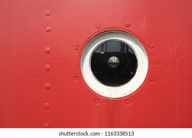 Detail of a round porthole with the red ship wall