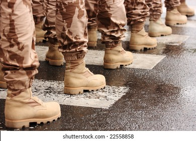 Detail of a row of soldiers wearing military boots on a zebra crossing