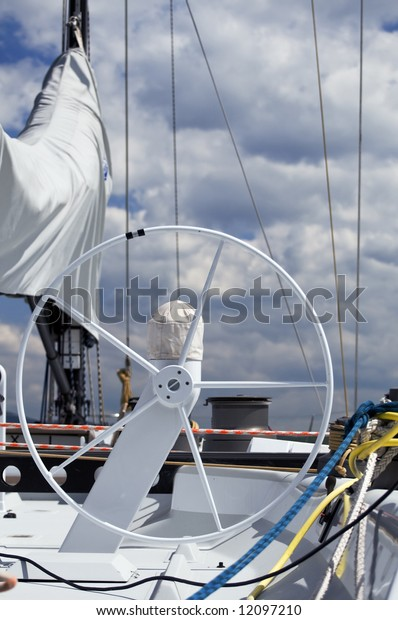 Detail of rudder and equipment on a sailboat against a cloudy sky
