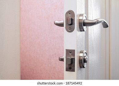 Detail of a safety or security lock on a white toilet's door. The lock can be open with a simple coin.