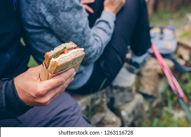 Detail of a sandwich that a couple is going to eat making a break to do trekking