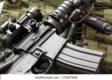 Detail of a scratched M4A1 (AR-15) carbine and green military tactical vest