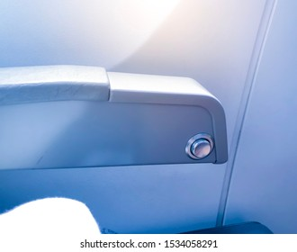 detail of seat adjustment button on armrest in airplane. Close up of seat adjustment control in economy class.