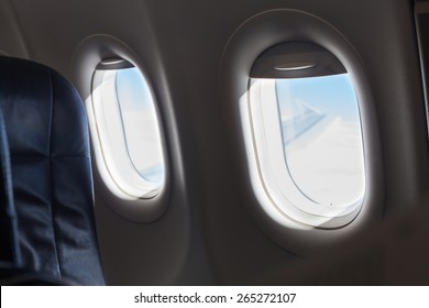Detail of seat and windows inside an aircraft.