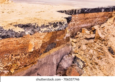Detail section of layers of soil beneath damaged asphalt road.