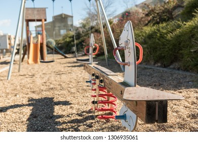 Detail of a seesaw and other swings in an empty park in a peripheral area of Caceres, Extremadura, Spain.