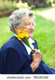 Detail of senior woman with yellow flower in the park or in a garden