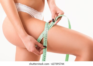Detail of a sexy woman's body in underwear with a measuring tape around her leg