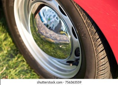 Detail of shiny hubcap of a red car on grass.