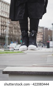 Detail of shoes of a stylish young man posing in an urban context