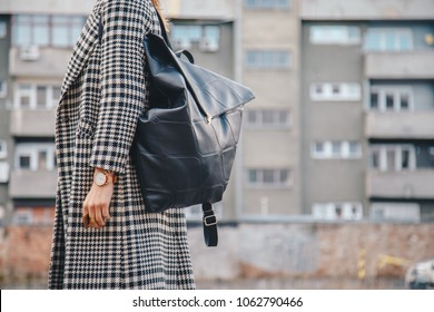 detail shot. attractive brunette woman outdoors posing in a checked patterned houndstooth coat, wearing a golden ring and watch and holding a black leather backpack. fashion outfit, streetstyle