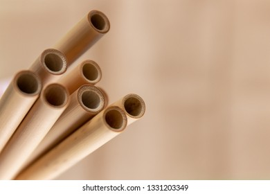 Detail shot of bamboo straws on a light brown background