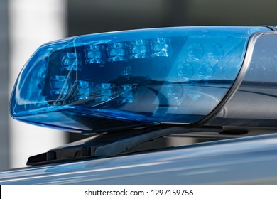 Detail shot of a blue light on a police car on the street