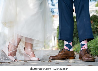 Detail shot of bride and groom's feet, shoes, and socks
