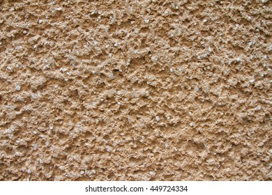 Detail shot of a bright-orange plaster wall with the stony deposits