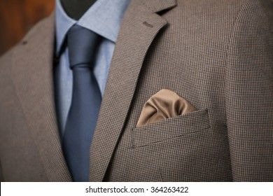 detail shot of a business suit: blue shirt, navy tie and brown coat