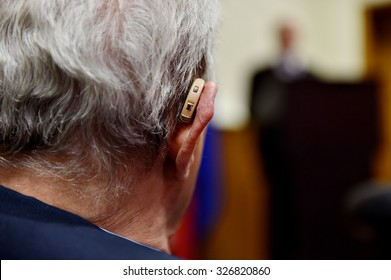 Detail shot with a hearing aid device used by old man during conference