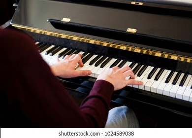 detail shot of a man hands backwards playing classic piano with both hands with natural light, dynamic shot hands in movement, music production concept, music learning concept.