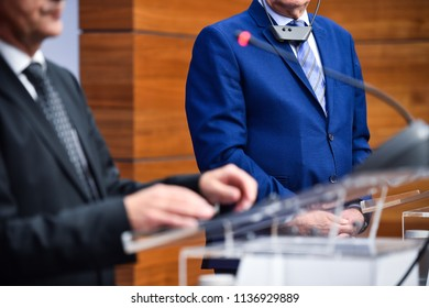 Detail shot with man in suits during a press conference