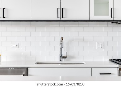 Detail shot of a modern kitchen sink with white cabinets, granite and subway tile.