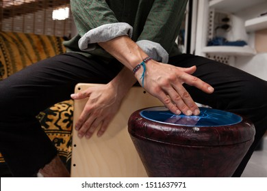 Detail shot of a multidisciplinary percussionist experimenting and creating sound combinations playing flamenco cajon drumbox and arabic darbuka at the same time. Music culture fusion concept.