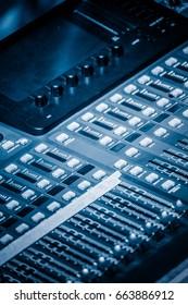 detail shot of recording studio mixing desk in blue tone.