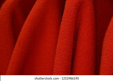 detail shot of red sleeves from some fleece jackets on hanger, colorful polar fleece jackets on a hanger macro shot made of recycled plastic bottles