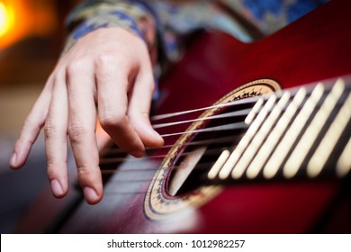 Detail shot of the right hand of a flamenco guitarist playing notes in the strings of his spanish acoustic guitar, musicology concept, flamenco, rumba, classical guitar. Music production concept.