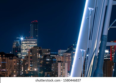Detail shot of the Walterdale bridge in Edmonton Alberta. Rivet marks are visible. The structure of the bridge is a foreground with the city and red lights being visible in the background. Night.