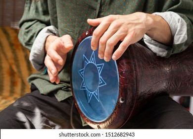Detail shot of a white man´s hands playing arabic darbuka. Arabic percussion sounds concept and music learning concept.