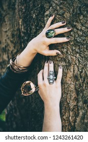 detail shot of womans hands with jewllery, holding round sunglasses, outdoors in a park