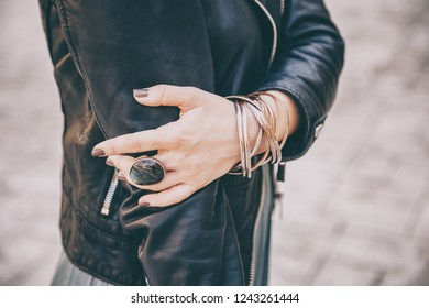 detail shot of womans hands, wearing a biker leather jacket and lots of jewllery on her fingers