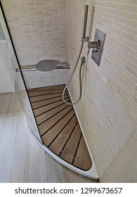 detail of shower tray in the modern bathroom with wooden floor and marble walls
