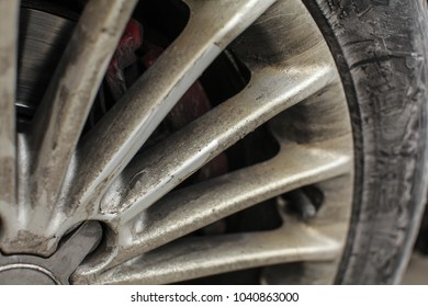 Detail of silver car rim and tire, very dirty from oil and dust.