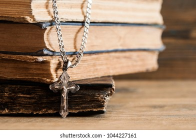 Detail of a silver small crucifix with an old books on a wooden table