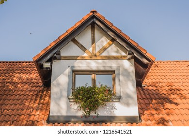 Detail of single old skylight window on an older rural vintage house with red shingles. So called dormer.
