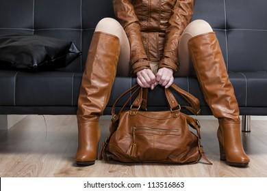 detalle de una mujer sentada con ropa marrón sosteniendo un bolso