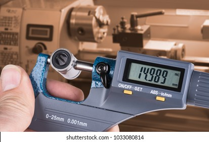 Detail of skilled worker's hand with digital micrometer screw gauge. Accurate measurement of metal linear bearing by measuring tool and lathe in background.
