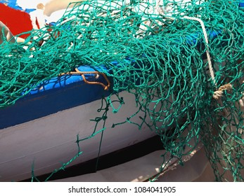 Detail of a small wooden fishing boat, which has the colors white and blue. Above it threw a bright green fishing net.