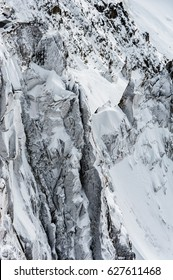 Detail of snow and ice covered cliffs and rockface on glacial mountain side off the side of the Mont Blanc in winter