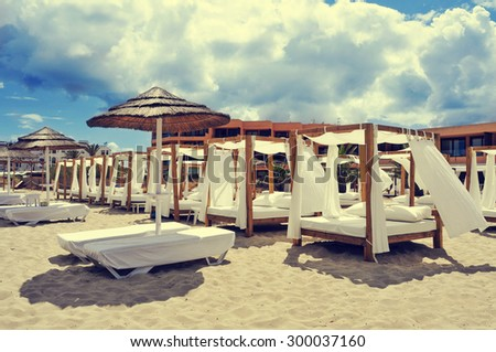 detail of some beds and sunloungers in a beach club in a white sand beach in Ibiza, Spain