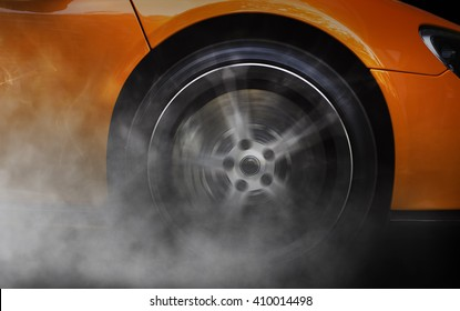 Detail of a sport car with spinning wheel, smoking, doing drifts and burnouts