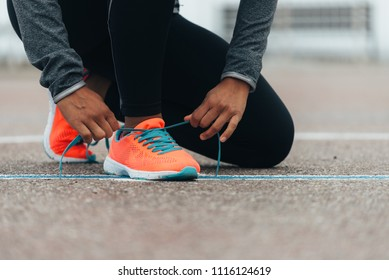 Detail of sporty swman lacing running shoes before before training. Outdoor city workout concept. Female fitness athlete getting ready for working out.