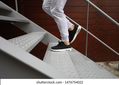 Detail of sporty woman running shoes while she is training climbing stairs. Urban fitness outdoor workout.