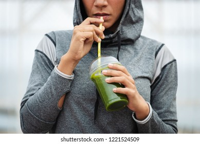 Detail of sporty woman taking a rest for drinking nutritive detox smoothie. Fitness nutrition and outdoor workout concept.