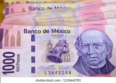 Detail of a stack of Mexican MXN banknotes with a denomination of 1000 pesos, showing obverse side of bill with image of Miguel Hidalgo y Costilla. One thousand Mexican peso notes, horizontal view.
