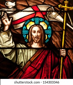 Detail of stained glass window depicting Easter resurrection of Jesus Christ, with Easter banner