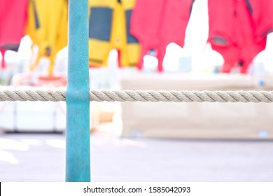 A detail of a stanchion and a lifeline on a classic sailing boat, foul weather clothing hung to dry in soft focus background.